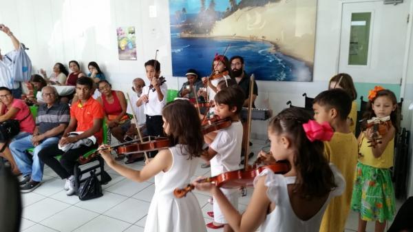 Crianças tocam violino para pacientes renais durante sessão de hemodiálise